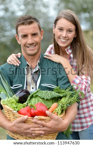 Portrait of couple of farmers holding basket of vegetables - stock photo
