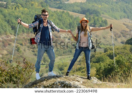 Portrait of couple of happy hikers in the countryside - stock photo