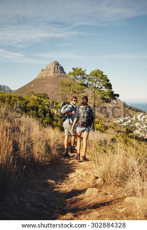 Portrait of couple of hikers walking through pathway on mountain. Man and woman enjoying summer vacation in countryside during a summer day. Young people hiking in nature. - stock photo