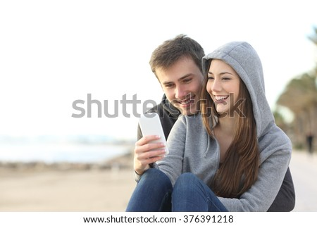 Portrait of couple of teenagers watching media content in a smart phone outdoors in the beach - stock photo