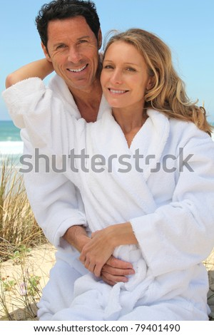 Portrait of couple on dunes in toweling robes - stock photo