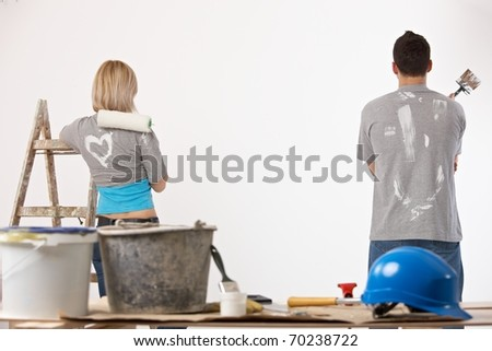 Portrait of couple painting at home, holding paint roller and brush, looking at wall.? - stock photo