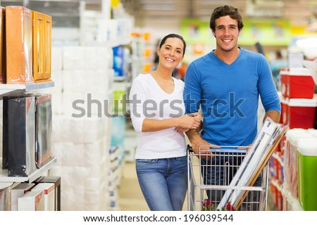 portrait of couple shopping together at supermarket - stock photo