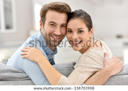 Portrait of couple sitting in sofa at home - stock photo