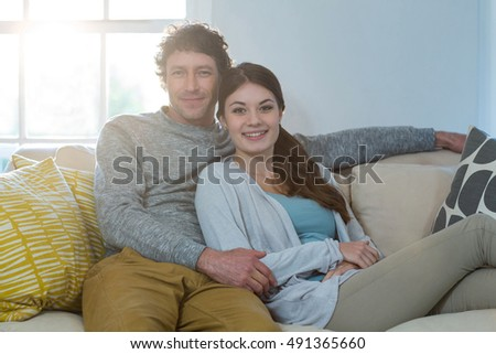Portrait of couple sitting on sofa at home