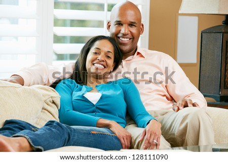 Portrait Of Couple Sitting On Sofa Together - stock photo