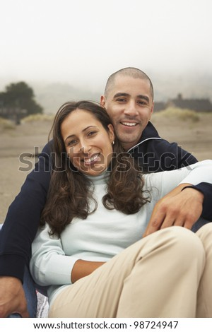 Portrait of couple sitting together at beach