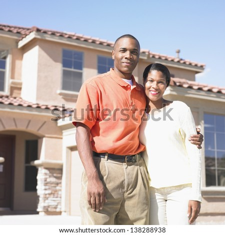 Portrait of couple standing in front of house - stock photo
