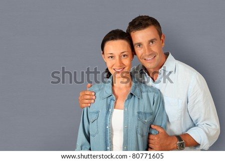 Portrait of couple standing on grey background - stock photo