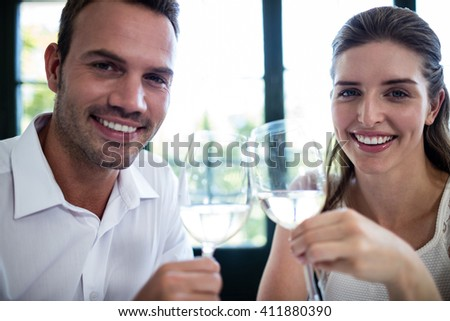 Portrait of couple toasting wine glasses at dining table in a restaurant - stock photo