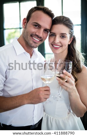 Portrait of couple toasting wine glasses in a restaurant - stock photo