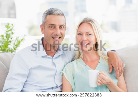 Portrait of couple with coffee cup sitting on sofa at home