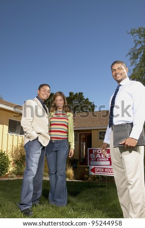 Portrait of couple with realtor at open house - stock photo