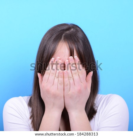 Portrait of covering her face with hands against blue background