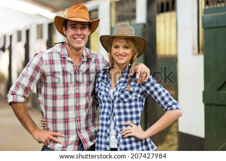 portrait of cowboy cowgirl couple inside stable - stock photo