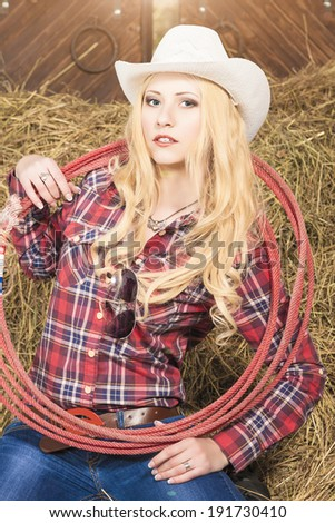 Portrait of Cowgirl With Lasso Rope in Cattleshed. Lighting Effect Used. Vertical Image - stock photo