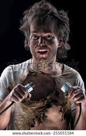 Portrait of crazy electrician over black background - stock photo