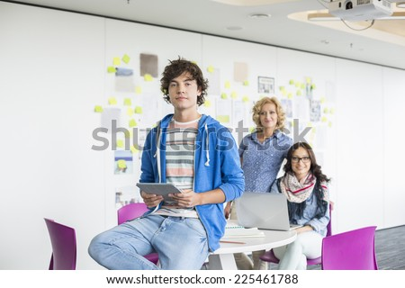 Portrait of creative businessman holding digital tablet with female colleagues in background - stock photo