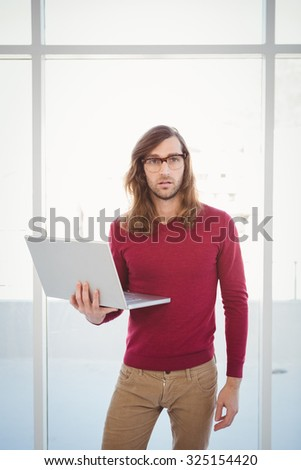 Portrait of creative businessman holding laptop while standing against window in office - stock photo