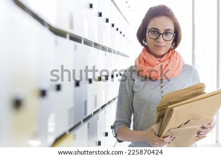Portrait of creative businesswoman holding envelopes in locker room at office - stock photo