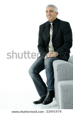Portrait of creative looking businessman wearing jeans and black jacket, sitting on couch. Isolated on white.