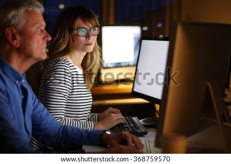 Portrait of creative team working at agency late night. Senior professional man and middle age designer woman sitting in front of computer monitor and working together on new project.  - stock photo