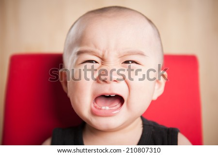 Portrait of crying baby boy sit on chair - stock photo