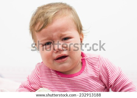 Portrait of crying baby nine-month girl. - stock photo