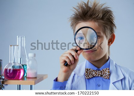 Portrait of curious boy looking through magnifier - stock photo