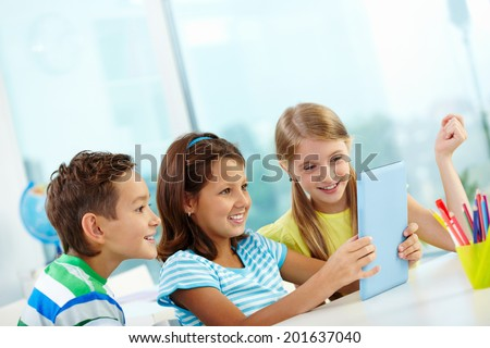 Portrait of curious classmates at workplace looking astonishingly at screen of digital tablet - stock photo