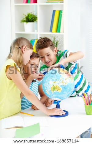 Portrait of curious classmates at workplace studying globe in classroom - stock photo