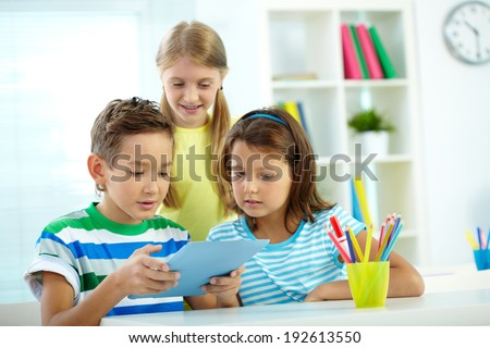 Portrait of curious classmates at workplace using digital tablet - stock photo