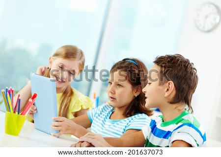Portrait of curious classmates at workplace using digital tablet