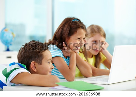 Portrait of curious classmates watching something interesting in laptop - stock photo