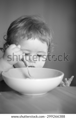 Portrait of curious small pretty male kid with curly hair and round cheecks eating from plate with spoon black and white closeup, vertical picture - stock photo