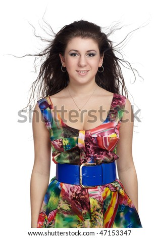 portrait of curly brunette girl posing in colorful dress on white
