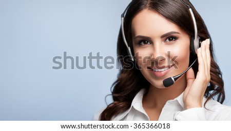 Portrait of customer support female phone worker, against grey background, with blank copyspace area for slogan or text - stock photo