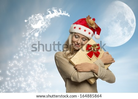 portrait of cute adorable blonde female with christmas hat and golden dress embracing her gift box     - stock photo