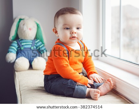 Portrait of cute adorable Caucasian baby boy in orange shirt onesie, jeans with suspenders barefoot sitting with bunny toy on windowsill looking away, natural window light, lifestyle - stock photo