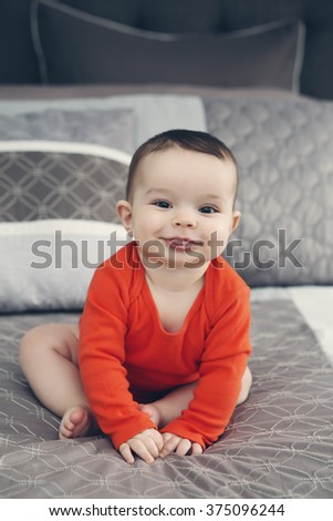Portrait of cute adorable Caucasian smiling baby boy girl with black eyes in orange onesie sitting on bed looking directly in camera showing tongue, natural window light, lifestyle - stock photo