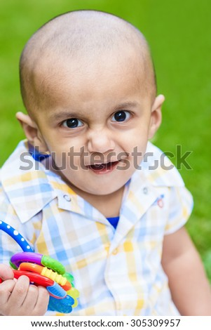 Portrait of cute adorable smiling laughing little indian mixed race infant boy with funny hilarious face expression in plaid shirt on green grass park background playing with toy