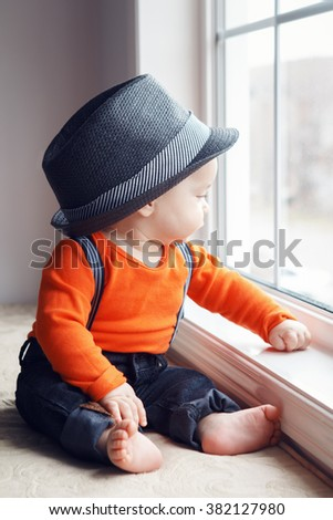 Portrait of cute adorable stylish Caucasian baby boy in hat, orange shirt onesie, jeans with suspenders barefoot sitting on windowsill looking away, natural window light, lifestyle - stock photo