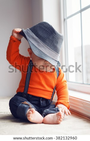 Portrait of cute adorable stylish Caucasian baby boy in orange shirt onesie, jeans with suspenders barefoot sitting on windowsill taking off his hat , natural window light, lifestyle - stock photo