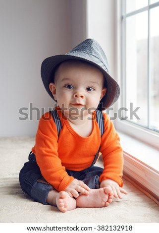 Portrait of cute adorable stylish Caucasian baby boy with black eyes in hat, orange shirt onesie, jeans with suspenders barefoot sitting on windowsill looking in camera, natural window light - stock photo