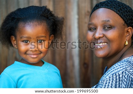 Portrait of cute African girl next to mother. - stock photo