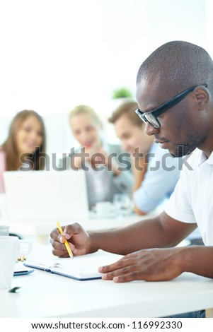 Portrait of cute African guy planning work with group of partners on background - stock photo