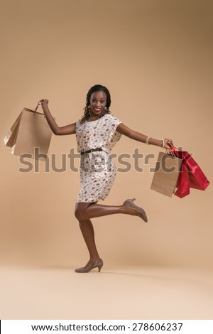 Portrait of cute african woman posing - shopping with paper bags full length portrait