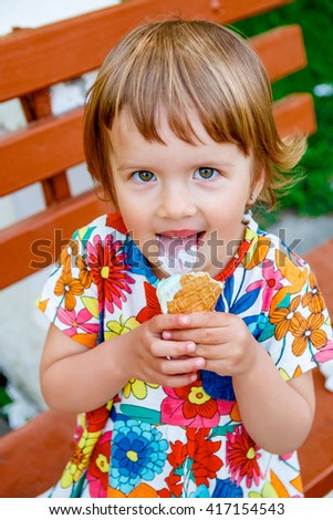 Portrait of Cute and happy little girl licking an ice cream outside.  Yummy ice cream.