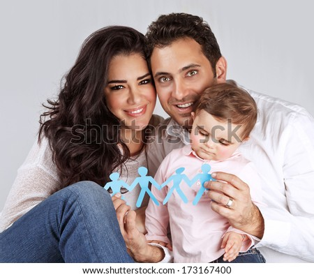 Portrait of cute arabic family sitting in the studio and holding in hands blue men-shape bonding paper, connection of people concept - stock photo
