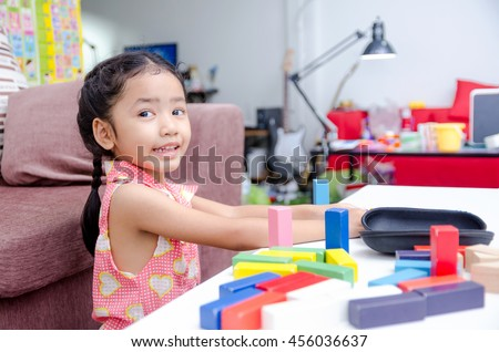 Portrait of cute asian little girl playing brick on table at home shallow depth of field